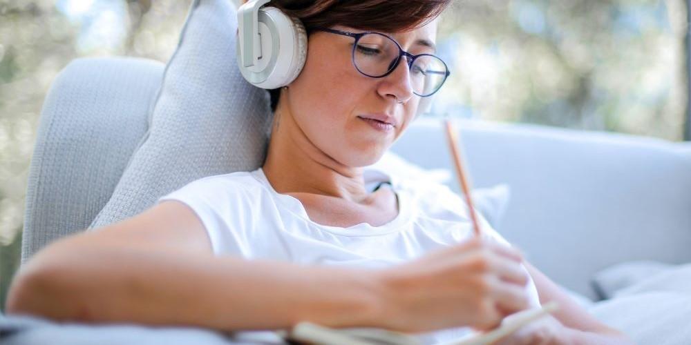 Blogbeitrag Schreiben mit Musik - Bild zeigt eine Frau mit Kopfhörern beim Schreiben.