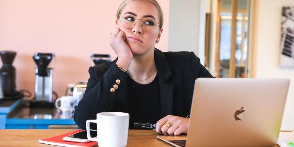 Blogbeitrag zum Thema Schreibblockade - Bild zeigt eine Frau, die frustriert vor ihrem Laptop sitzt