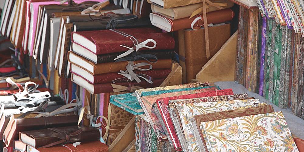 Über mich Seite der Schreibtrainerin und Gateless Writing Teacher Christine Kämmer - Bild zeigt einen Stapel von Notizheften auf einem Markt