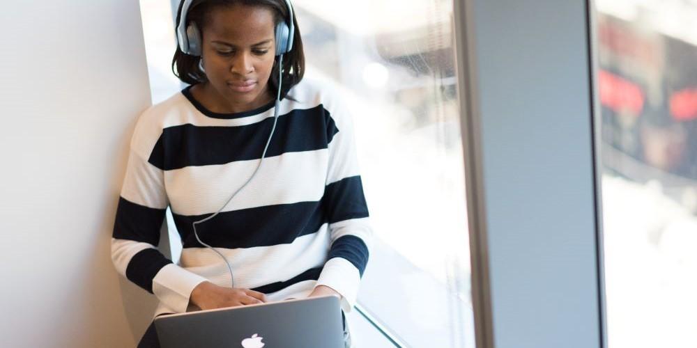 Blogbeitrag zum Thema Schreiben mit Musik. Bild zeigt eine Frau mit Kopfhörern, die am Laptop tippt.